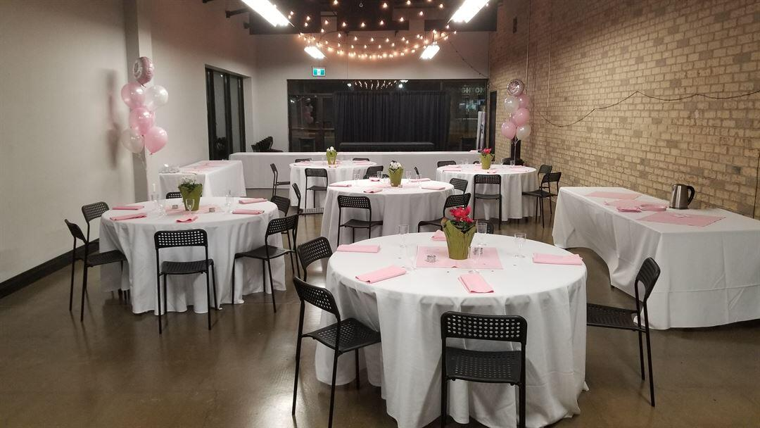 Photo of event hall with round tables and string lights